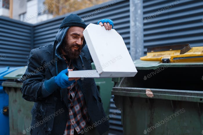 Bearded dirty beggar found pizza in trashcan