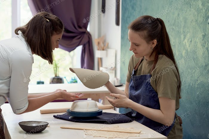 Female ceramist teaching young student shaping and molding in workshop