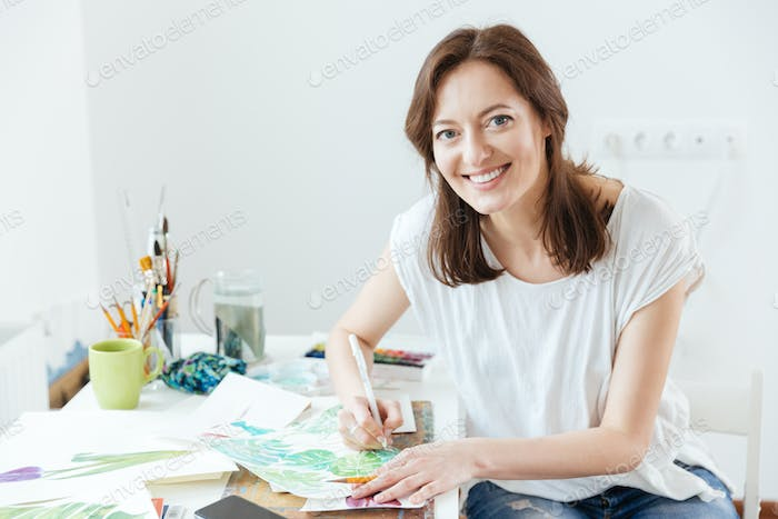 Cheerful woman artist sitting and drawing in art studio