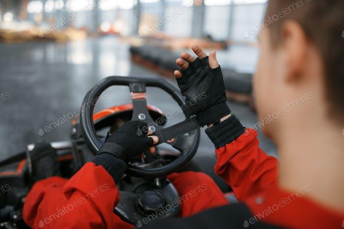 Kart racer in red uniform puts on gloves