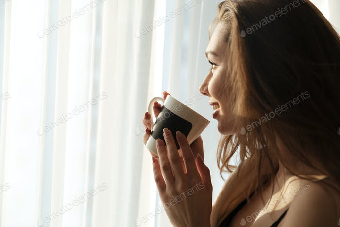 Happy lovely young woman standing and drinking coffee at home
