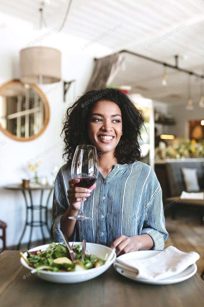 Beautiful African American lady happily looking aside with glass of wine in hand at cafe