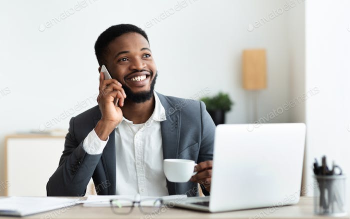 Businessman talking on mobile phone and drinking coffee at workplace