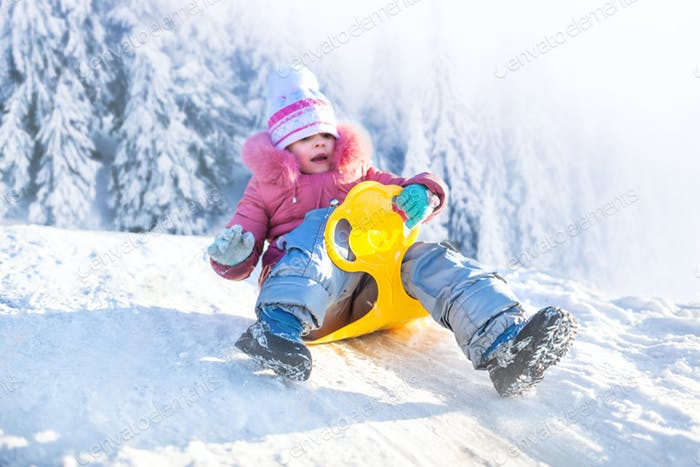 Happy small girl in winter clothing riding downhill on snow with winter