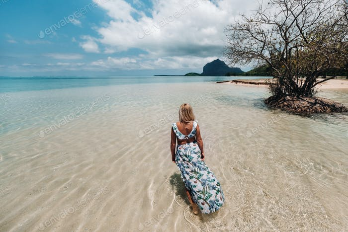 Young woman in a swimsuit relaxing on a tropical beach. Tropical vacation in paradise.mauritius