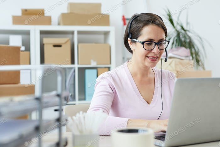 Happy helpdesk operator consulting clients online