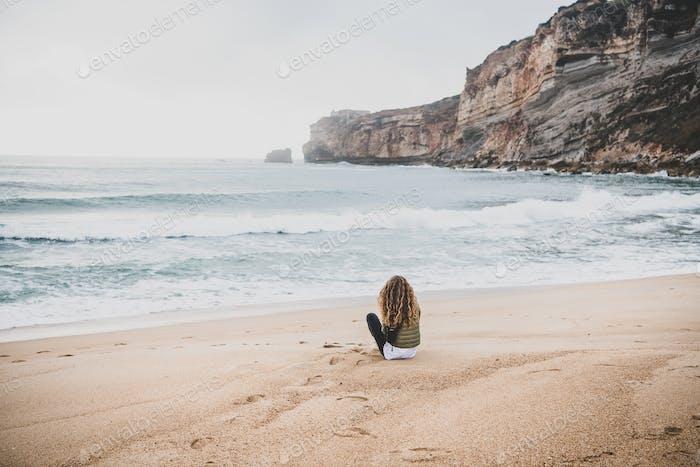 Woman sitting at Atlantic ocean beach in Portugal