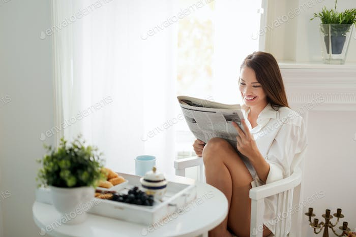 Beautiful young woman reading magazine at home