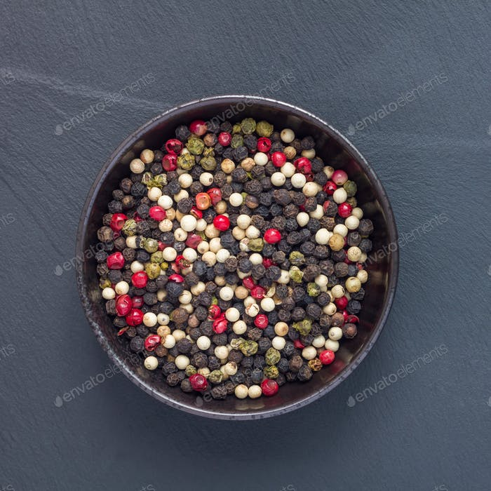 Four different kinds of peppercorns in clay bowl on stone background, top view, square