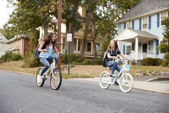 Two teen girlfriends ride past on bikes in a quiet street