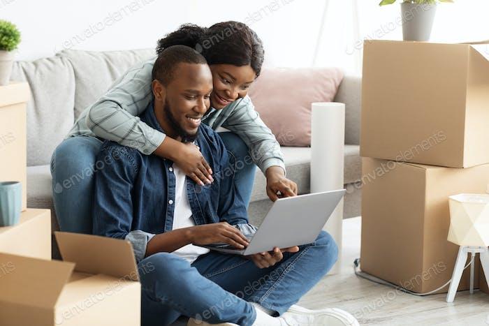Pedido online. Feliz pareja negra joven con computadora portátil eligiendo muebles en Internet