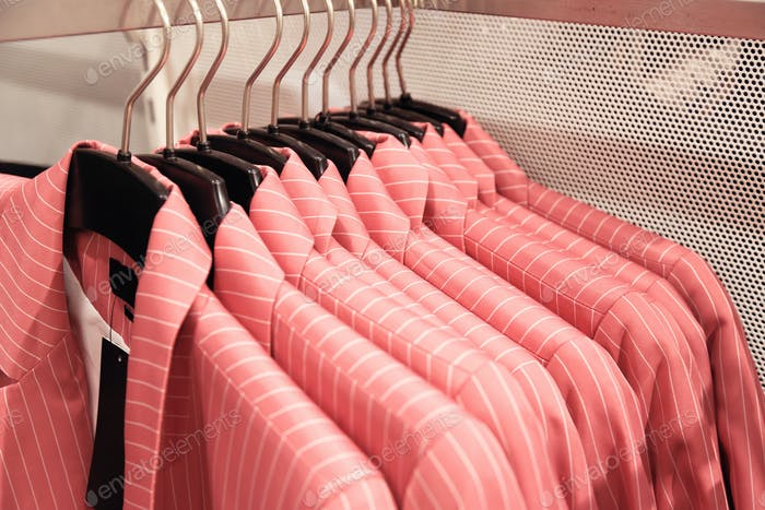 Pink women's jackets in stripes on a hanger in a store.