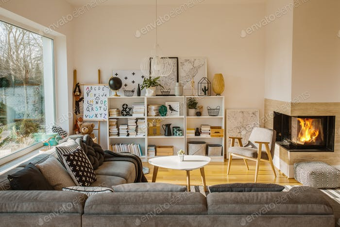 White Scandinavian living room interior with fireplace, posters,