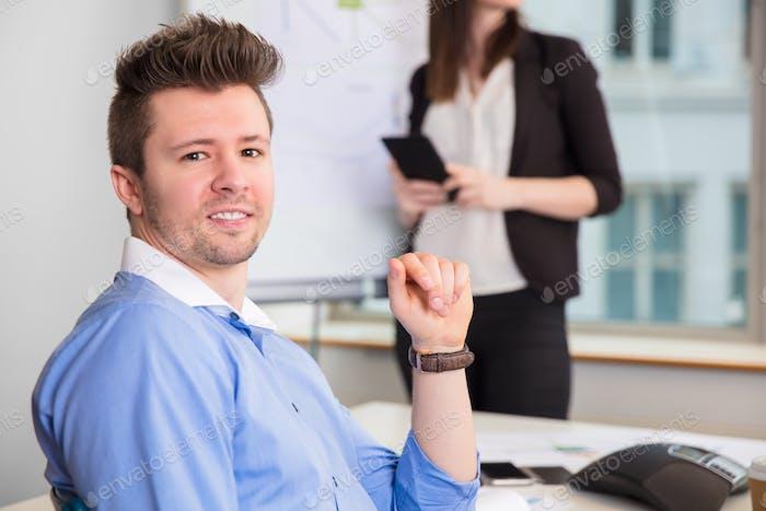 Selbstbewusster Geschäftsmann lächelnd während Kollege stehen im Büro