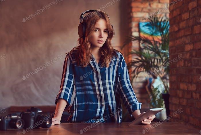 Ein junges charmantes sinnliches Mädchen hören eine Musik in Kopfhörern