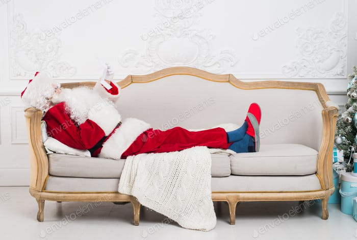 Santa claus using mobile phone at home during christmas time