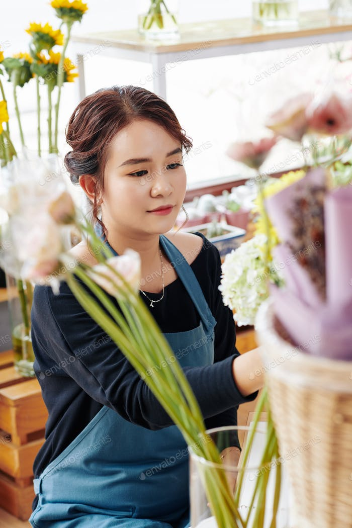 Young woman arranging flowers in store