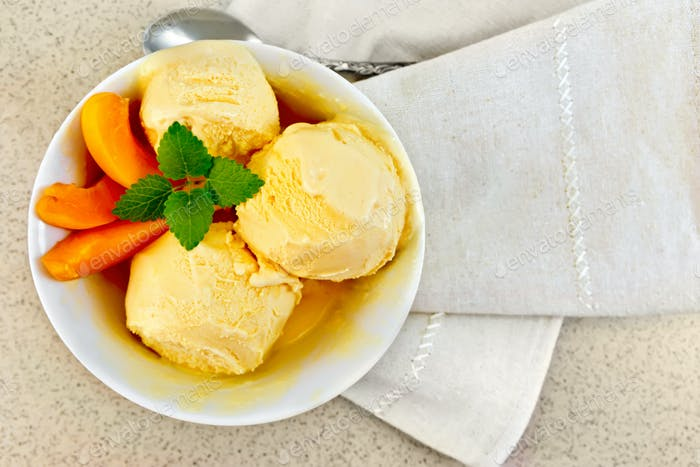 Ice cream apricot in white bowl on table top