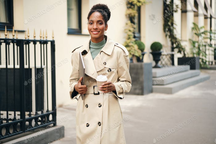 Attractive African American business woman in stylish trench coat with laptop and coffee outdoor