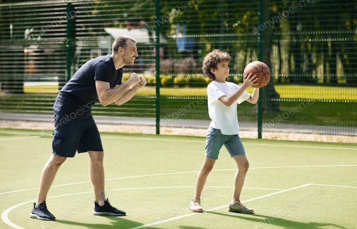 Boy playing basketball at playground, man cheering him