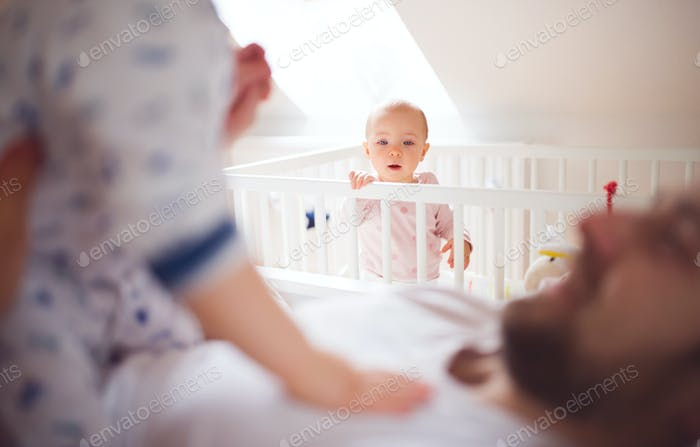 Father with toddler children in bedroom at home at bedtime.