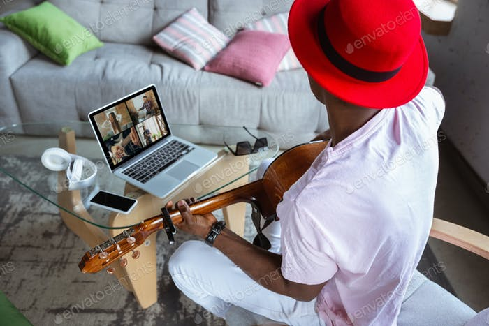 African-american musician playing guitar during concert at home isolated and quarantined, impressive