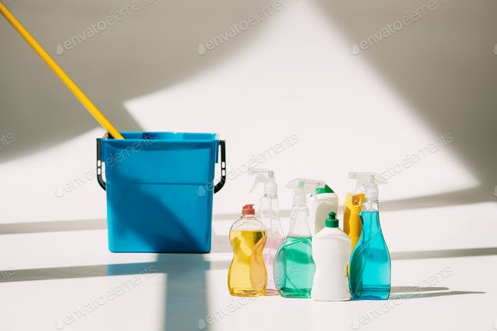 various cleaning products, mop and bucket on white