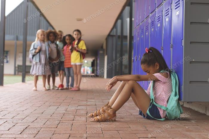 Schoolgirl sitting alone in school corridor while others school kids looking at her in background