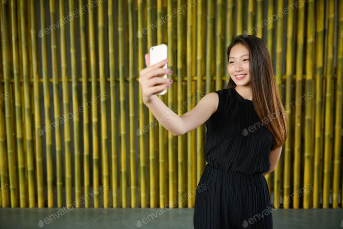 Happy young beautiful Asian businesswoman taking selfie against bamboo fence