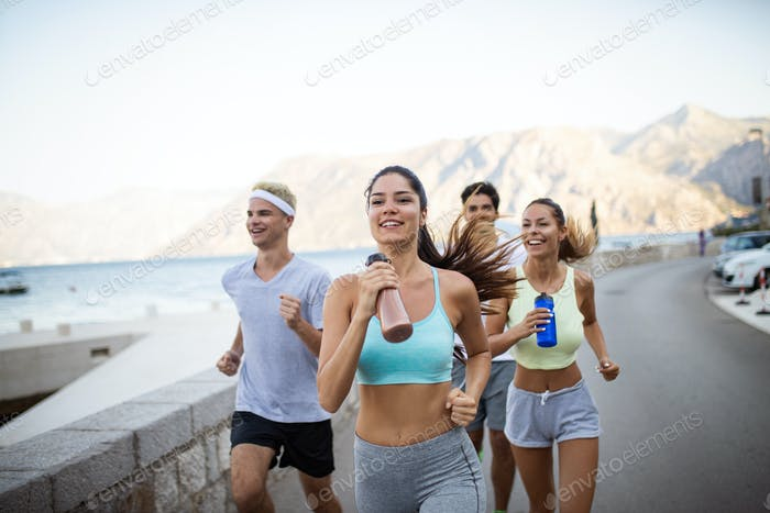Happy people jogging outdoor. Running, sport, exercising and healthy lifestyle concept