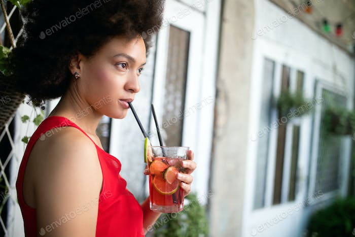 Lifestyle fashion portrait of woman posing on the street with drink