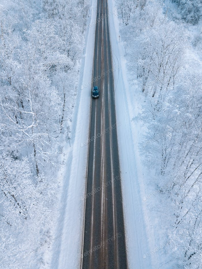 Aerial view of a winter road with snow forest