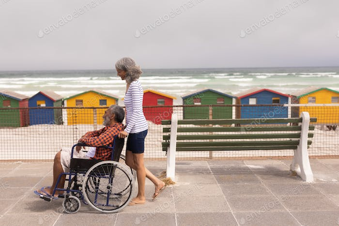 Side view of disabled senior man and senior woman walking on promenade at beach