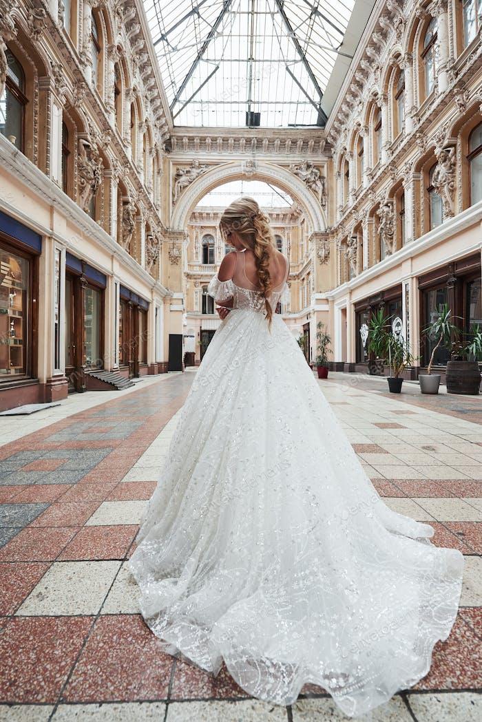 Schöne, elegante Braut mit einem perfekten Brautkleid, posiert um schöne Architektur