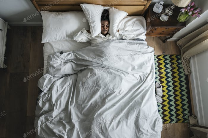 African American woman on bed insomnia and noise pollution concept