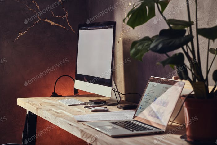 Tisch mit Computer und Laptop darauf