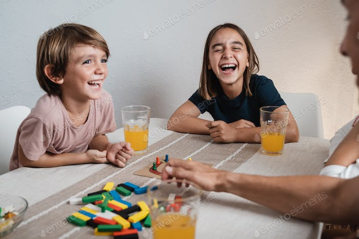 Happy hispanic family having fun playing board games with kids together at home - Focus on girl face