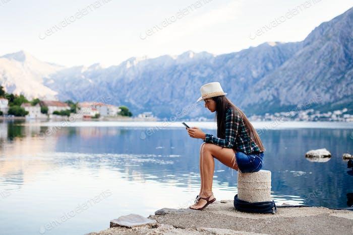 woman using smartphone on beach
