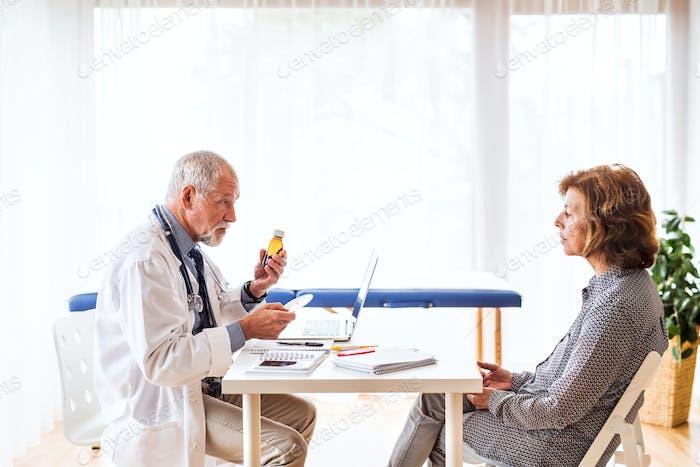 Arzt mit Laptop im Gespräch mit einer Seniorin im Büro.