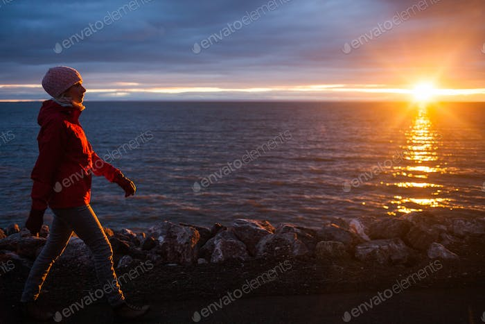 Young Woman Walking during Sunset on a Cold Evening