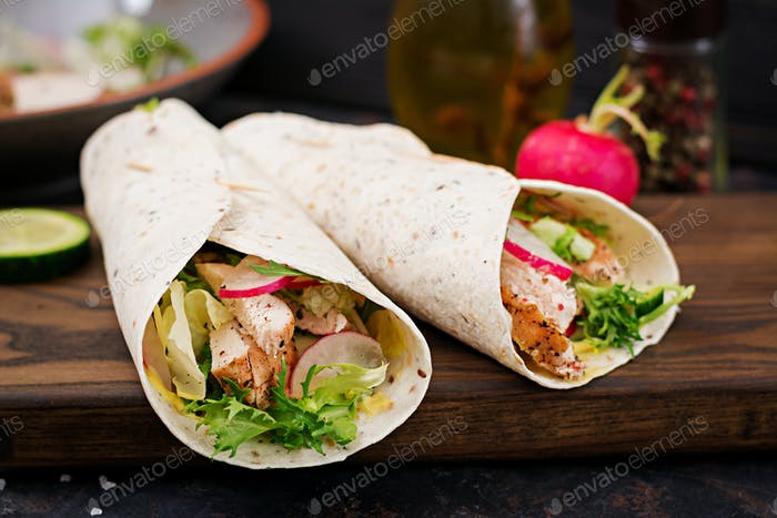 Healthy mexican tacos with baked chicken breast, cucumber, radish and lettuce.