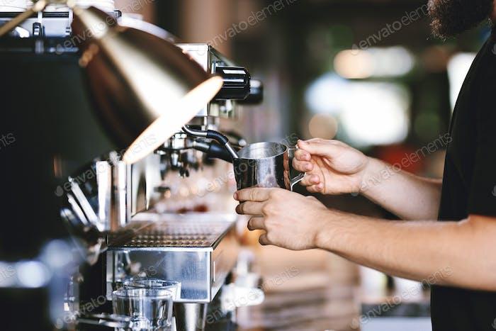 Eine moderne teure Kaffeemaschine wird in der Arbeit im modernen gemütlichen Café gezeigt