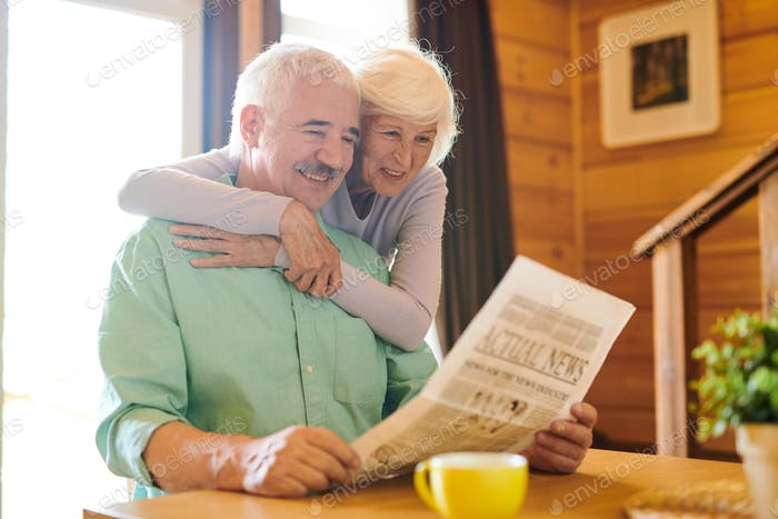 Cheerful senior couple in casualwear looking through latest news