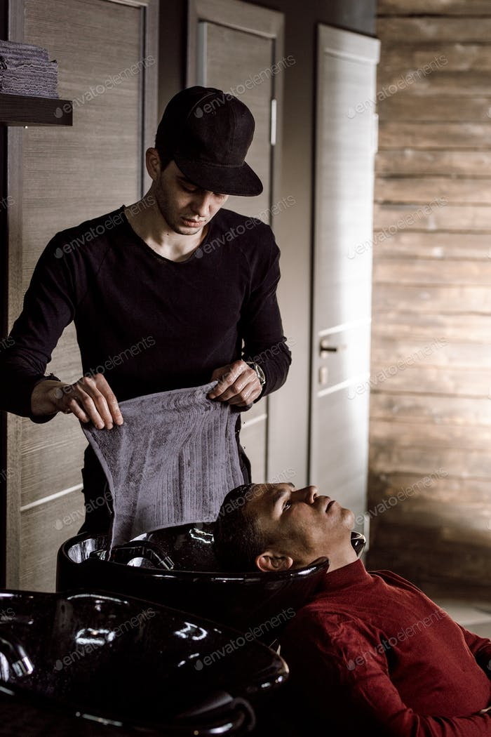 The barber dressed in black clothes washes the man's hair in a barbershop