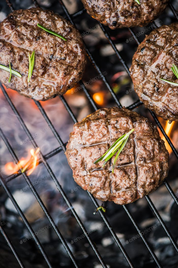 beef burgers on grill with flames