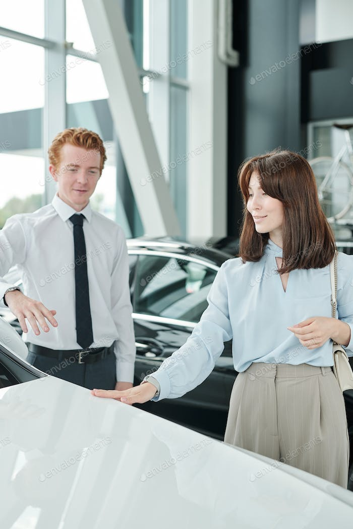 Elegant brunette female consumer looking at new luxurious car in auto center