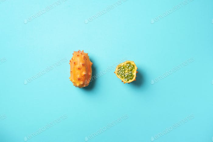 Kiwano or african horned melon on blue background. Top view. Cutted hedged gourd, african horned