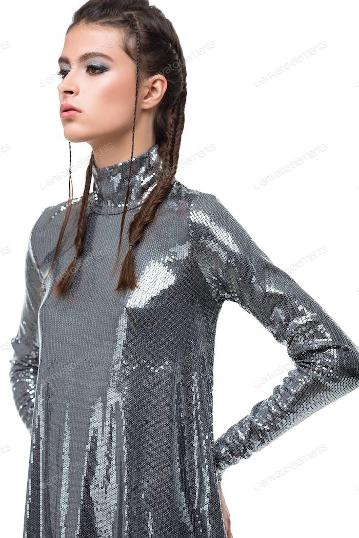 Porträt der jungen Dame stehend im Kleid in Pailletten und nachdenklich beiseite schauen