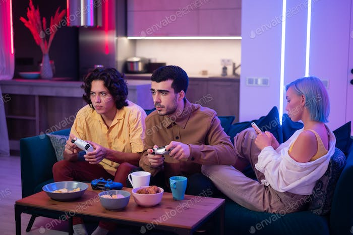 Two male friends excited to play video games at home while a girl sitting with them on a couch and