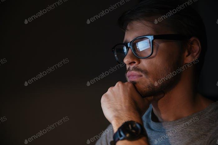 Closeup of focused man in glasses looking at screen